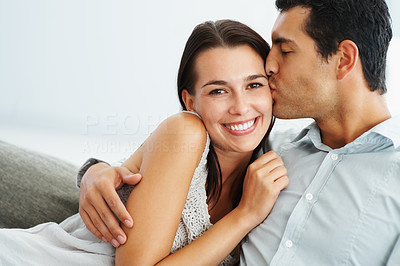 Buy stock photo Portrait of smart young man kissing his girlfriend on sofa