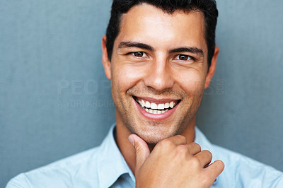 Buy stock photo Closeup portrait of smiling young man with hand on chin