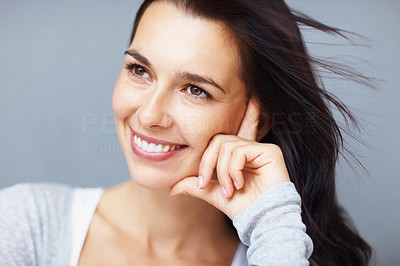 Buy stock photo Closeup of pretty young woman smiling while looking away, isolated on a neautral background