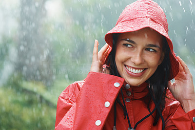 Buy stock photo Pretty woman smiling while holding rain coat hat while being rained on