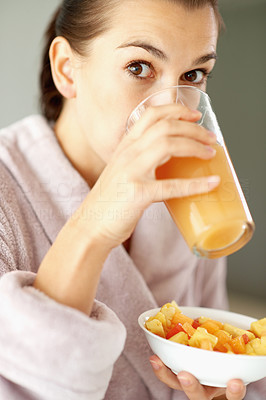Buy stock photo Portrait of young woman drinking juice and holding bowl of fruits salad