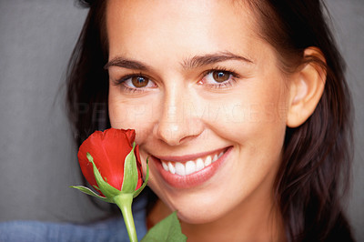 Buy stock photo Closeup of attractive young woman with red rose smiling