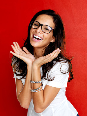 Buy stock photo Portrait of beautiful young female wearing glasses smiling against red background