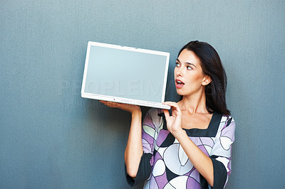 Buy stock photo Portrait of surprised young woman looking at laptop screen