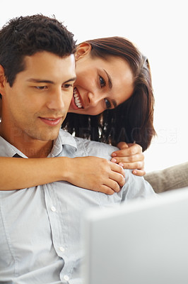 Buy stock photo Handsome man using laptop with woman embracing him from behind