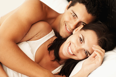 Buy stock photo Portrait of happy young couple lying in bed and smiling