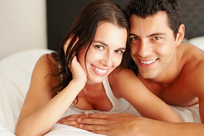 Buy stock photo Young couple lying together in bed and smiling