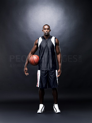 Buy stock photo Portrait of a young male basketball player standing with basketball against black background