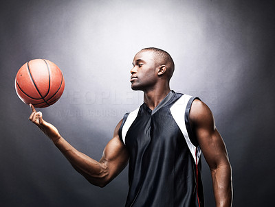 Buy stock photo Portrait of muscular young man spinning basketball on finger against grunge background