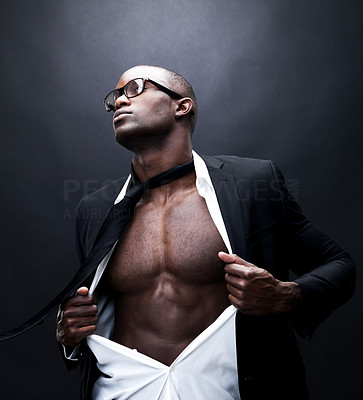 Buy stock photo Portrait of a young african american businesman pulling his shirt open revealing well built torso