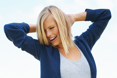 Buy stock photo Cheerful young woman with hands behind head standing outdoors