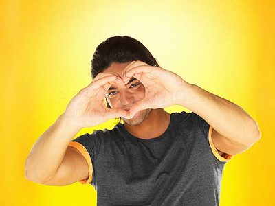 Buy stock photo Handsome man looking through heart sign