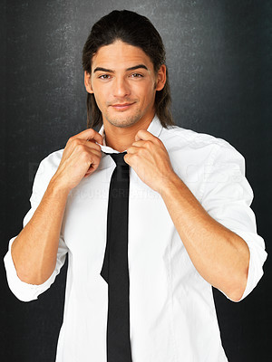 Buy stock photo Attractive man loosening his tie against gray background