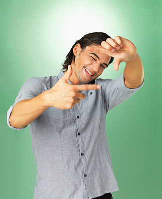 Buy stock photo Handsome man making a frame with his fingers as he squints with his head titled to one side