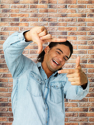 Buy stock photo Young male tilting his head while looking through a frame created with his hands