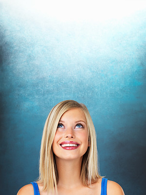 Buy stock photo Smiling young woman looking up at copyspace