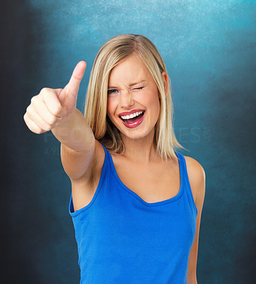 Buy stock photo Beautiful woman winking while giving thumbs up