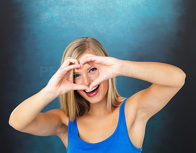 Buy stock photo Closeup of pretty woman looking through heart sign