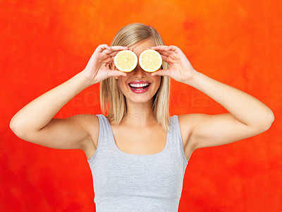 Buy stock photo Portrait of young woman holding lemons up to eyes and smiling