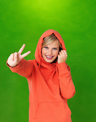 Buy stock photo Portrait of cheerful young woman showing victory sign in hooded sweatshirt