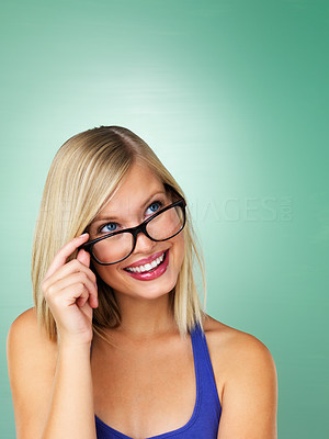 Buy stock photo Young girl holding glasses and looking up at copyspace
