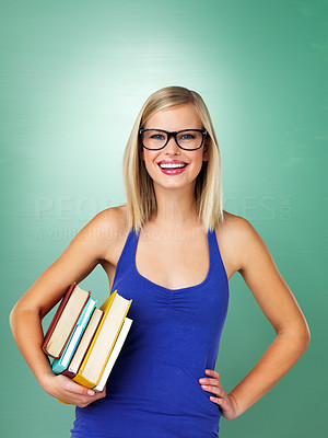 Buy stock photo Smiling student holding books on green background