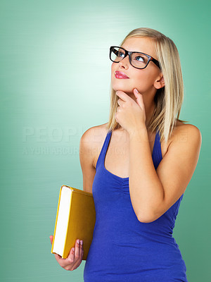 Buy stock photo Teenage girl in glasses holding book and looking up
