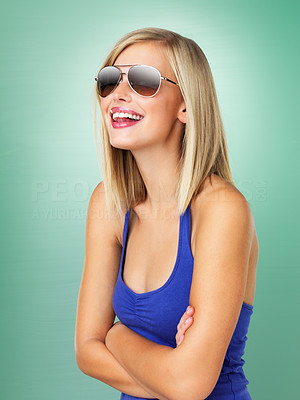 Buy stock photo Cheerful girl in sunglasses hands folded on green background
