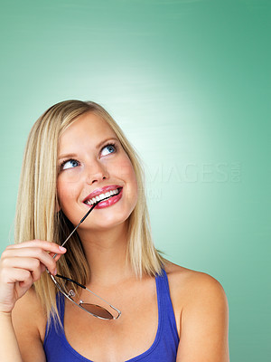 Buy stock photo Closeup of a pretty girl with sunglasses in her mouth looking up at copyspace, isolated on a fresh mint green