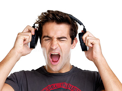 Buy stock photo Portrait of an unhappy young man getting disturbed by loud music against white background