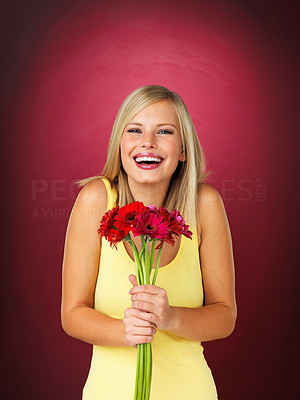 Buy stock photo Colourful portrait of a pretty blonde woman smiling happily, holding a bouquet of flowers against a maroon background