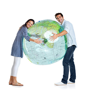 Buy stock photo Portrait of a happy young couple holding a globe against white background