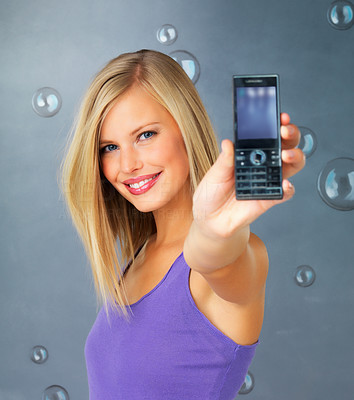 Buy stock photo Pretty blonde woman holding out cell phone
