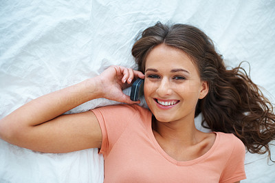 Buy stock photo Top view of teen girl lying on her bed talking on her cell phone