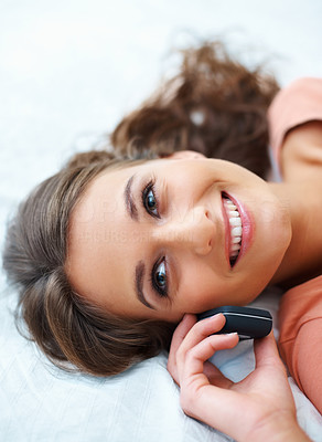 Buy stock photo Smiling teen listening on the phone while lying down