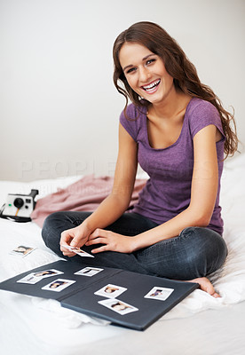 Buy stock photo Smiling girl sitting cross-legged on bed with photo album