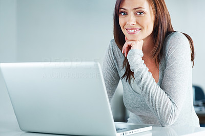 Buy stock photo Portrait of a beautiful young woman sitting with a laptop and smiling