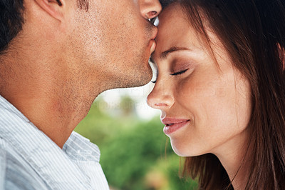Buy stock photo Closeup portrait of a young man kissing his cute girlfriend on forehead - Outdoor