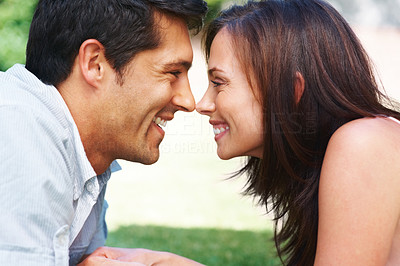 Buy stock photo Closeup portrait of a romantic young couple lying face to face - Outdoor