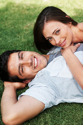 Buy stock photo Portrait of a lovely young couple relaxing on grass in the park - Outdoor