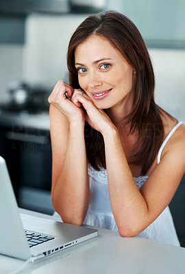 Buy stock photo Portrait of a relaxed young lady smiling with a laptop in the kitchen at home - Indoor