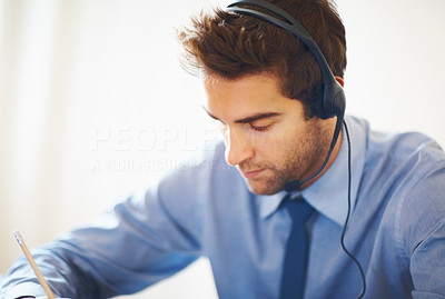 Buy stock photo Closeup portrait of young executive wearing headset and noting down
