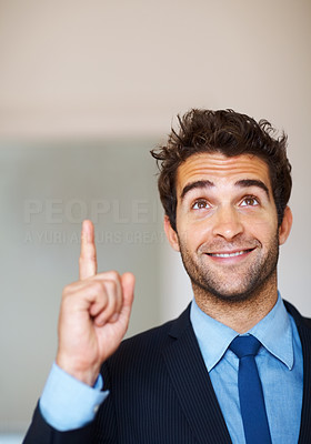 Buy stock photo Smiling executive pointing and looking upwards