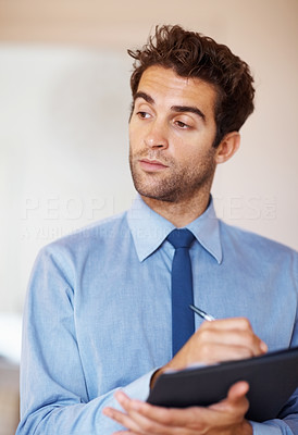 Buy stock photo Businessman observing and writing down notes on clipboard