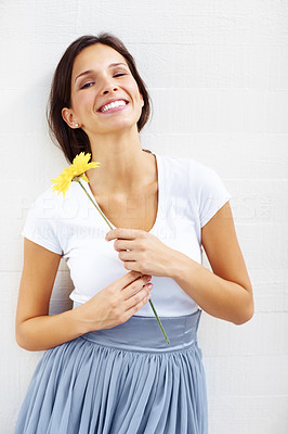 Buy stock photo Beautiful young woman holding a yellow flower and smiling against white background