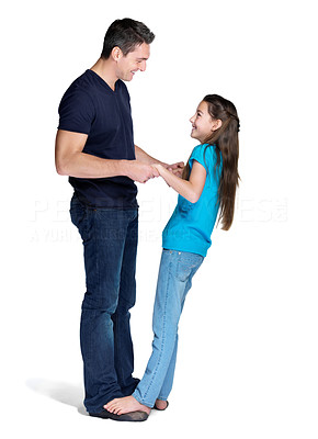 Buy stock photo Portrait of a cute small girl standing on her father feet while dancing over white background