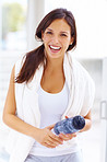Fit young woman holding a water bottle in gym