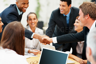 Buy stock photo Two male executives shaking hands during company meeting
