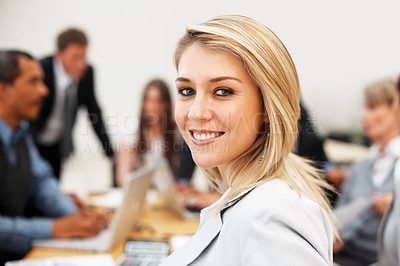 Buy stock photo Pretty executive during meeting with colleagues in background