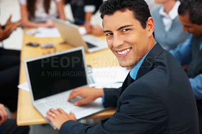 Buy stock photo Handsome business man working on laptop during meeting
